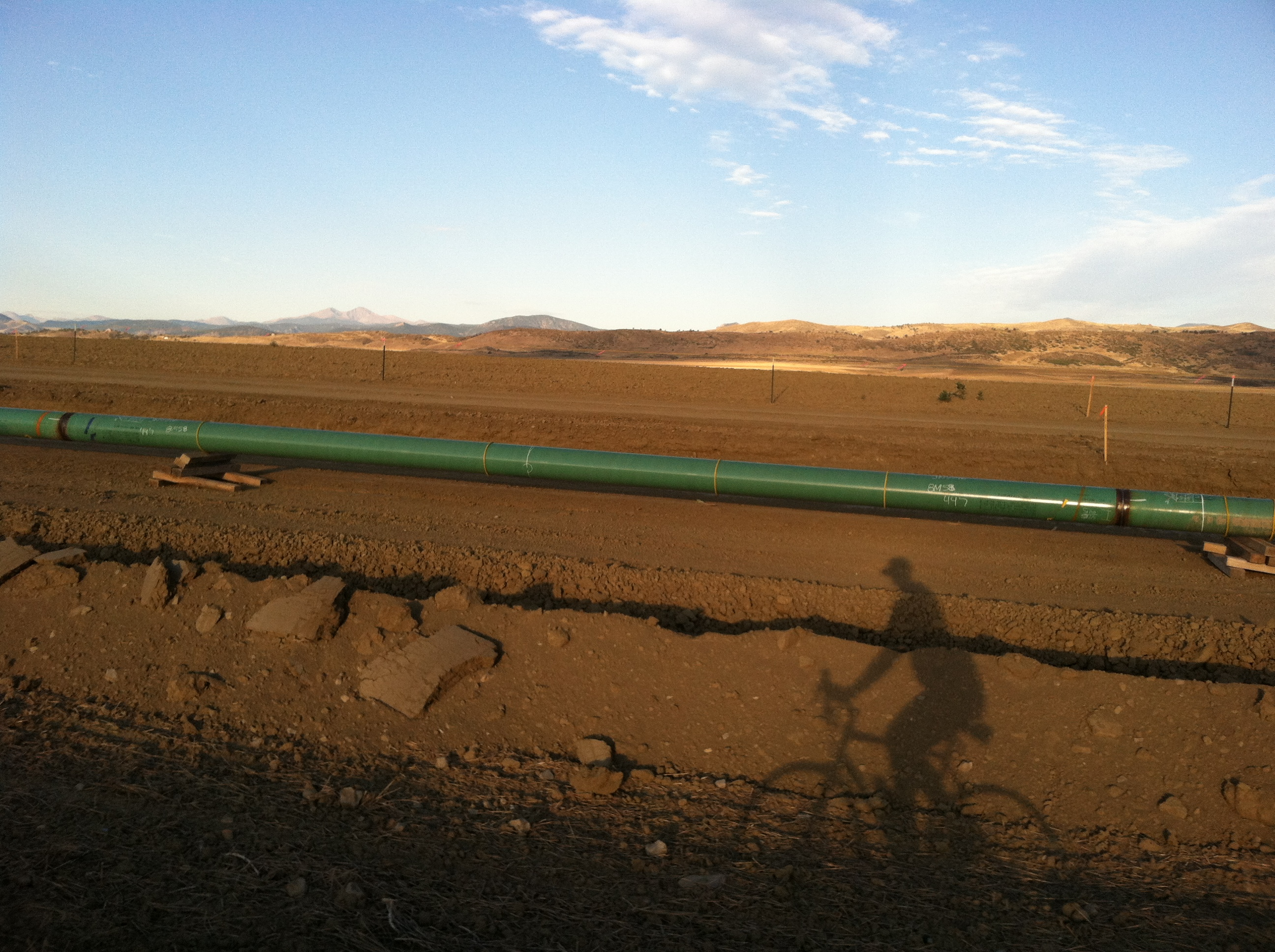 bike riding by gas pipeline near winter wheat fields